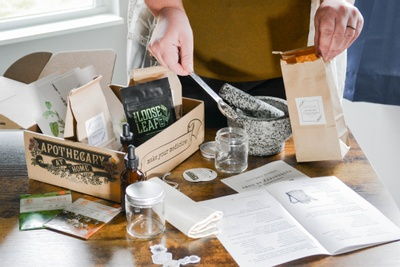 An Herbal Apprentice subscription box sitting on a table, filled with loose leaf tea packets. A person is filling packets.