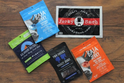Items from a Jerky Snob subscription box including 2 different kinds of Baja Jerky packs, and a 2 Chicks Turkey Jerky pack.