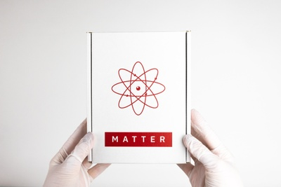 Gloved hands holding a closed, white Matter subscription box with an atom symbol on it.