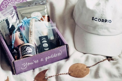 An open Goddess Provisions subscription box filled with crystals, aromatherapy, vegan beauty and superfood snacks.
