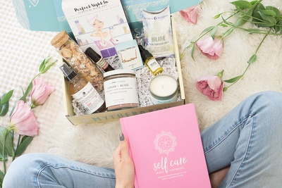 Seen from above, a woman holds a box that says My Therabox. It contains a pink self care book and several scented items.