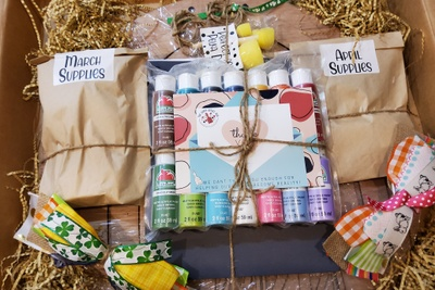 Items from a Easy Artist subscription box including brown paper bags labeled March Supplies and April supplies, and paints.
