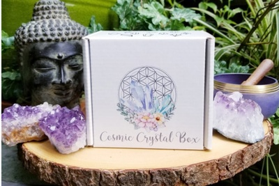 A Cosmic Crystal Box sits on a tree stump with amethyst crystals all around it.