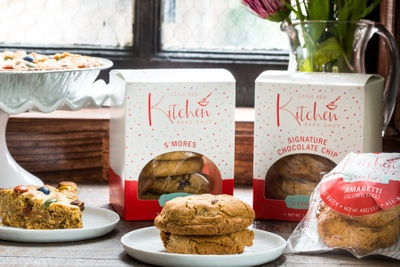 Cookies on a plate in front of subscription boxes of cookies labeled Little Red Kitchen.