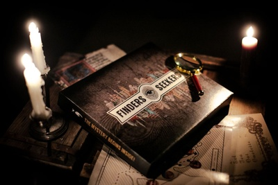 A Finders Seekers Escape Room Game subscription box with a magnifying glass on top and lit candles nearby.