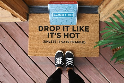 A person standing on a doormat that says Drop It Like It's Hot (Unless It Says Fragile) and there's a Smartass and Sass box.