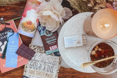 Items from an Authentic Books subscription box, including a lit candle, matches, tea, a chocolate bar and a flower.
