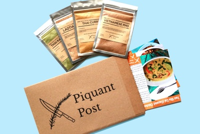 A Piquant Post subscription box with recipe cards coming out of it and 4 packets of seasonings.