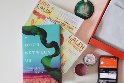 Items from a The Chaptr subscription box including a book, a small candle in a tin, and cocktail recipes.