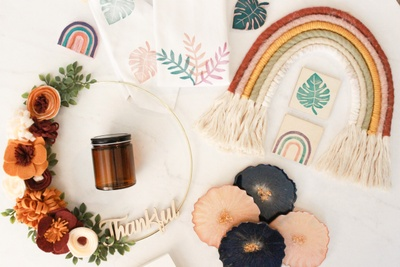 Items from a Craftee DIY subscription box including a knitted rainbow, dried flowers, leaf prints, and a small brown jar.
