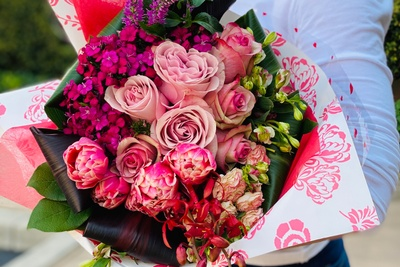 A bouquet of roses and other flowers in all shades of pink.