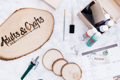 Items from the Adults and Crafts subscription box including slices of wood, wood burning tools and paints.