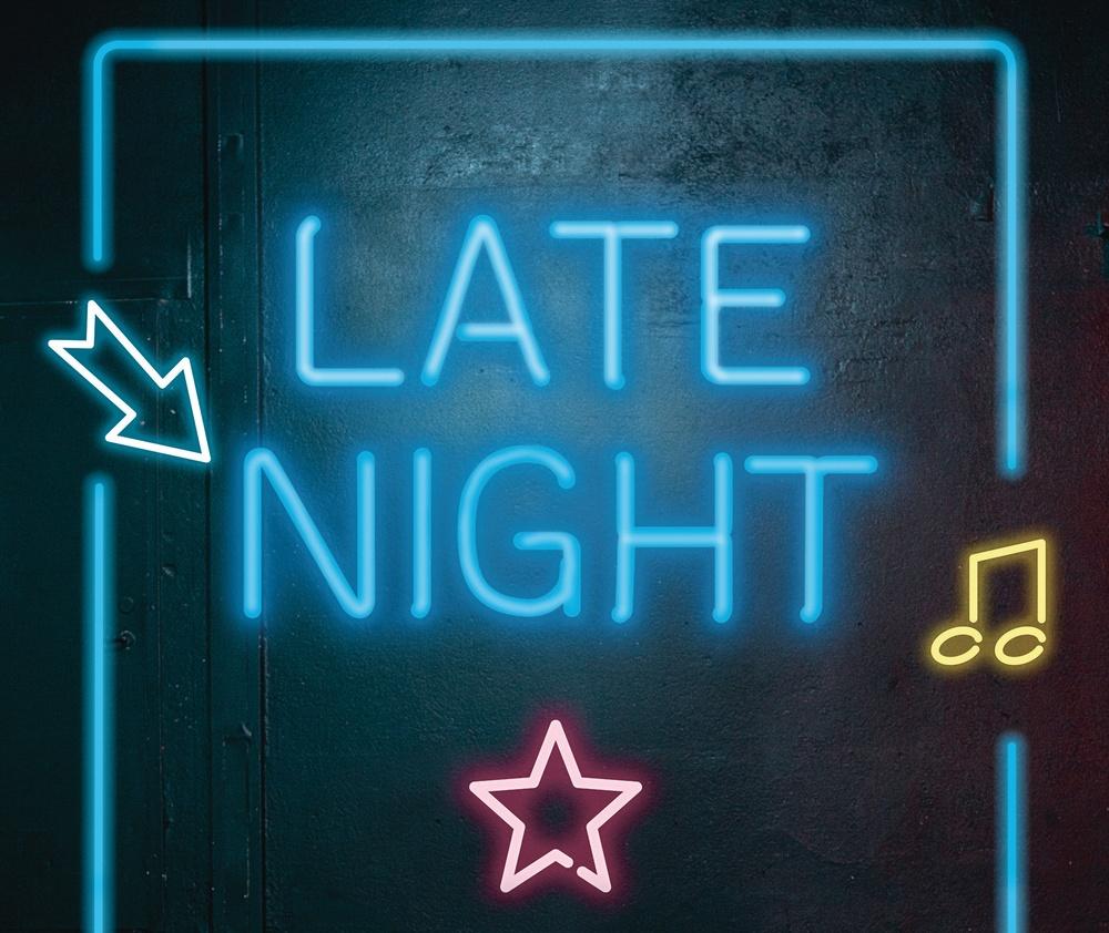 Namnet Late Night är en blå neonskylt som sitter på en svart scenvägg.