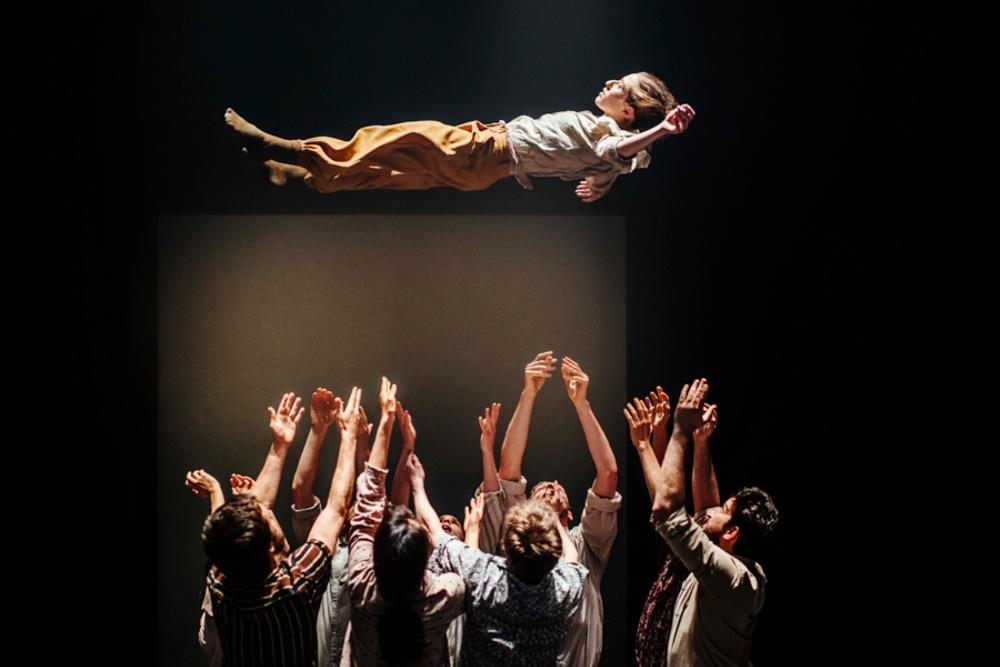 En dansare klädd i bruna byxor och vit skjorta kastas upp i luften av tio personer som alla står under hen med armarna upp i luften.