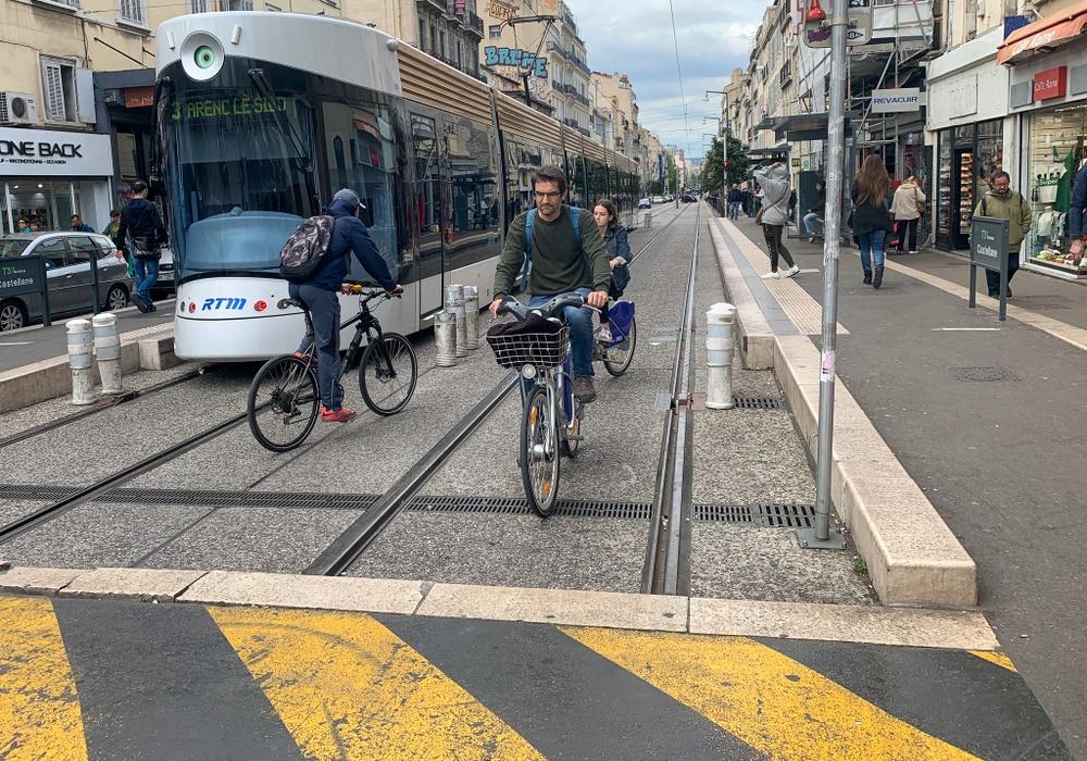 Spårvagn och cyklister delar på utrymme vid en av linjernas tillfälliga slutstationer.
