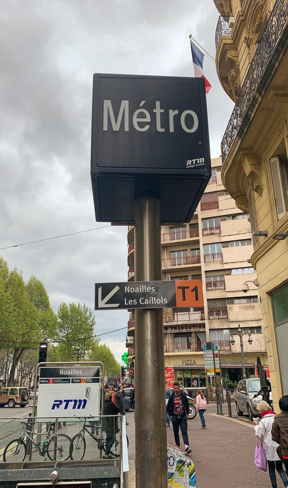 Bild på metroskylt med infoskylt om spårvägen som är svår att se.