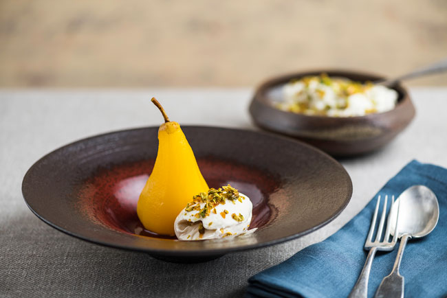 Saffron and perry-poached pears with honey cream and pistachio