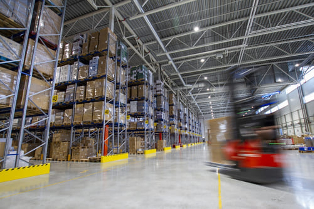 A red forklift driving in a warehouse of Europris