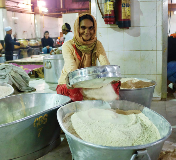 Sieving flour for chapattis at Gurudwara Bangla Sahib, Delhi