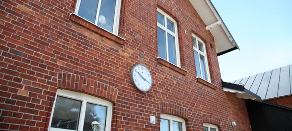 Tegelbyggnad som har en klocka på gaveln