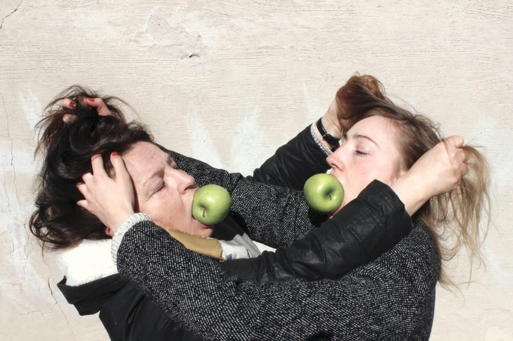 Två kvinnor står mitt emot varandra och drar i varandras hår. I munnen har dom ett varsitt grönt äpple. De har båda svarta kläder och väggen bakom dom är ljust beige.