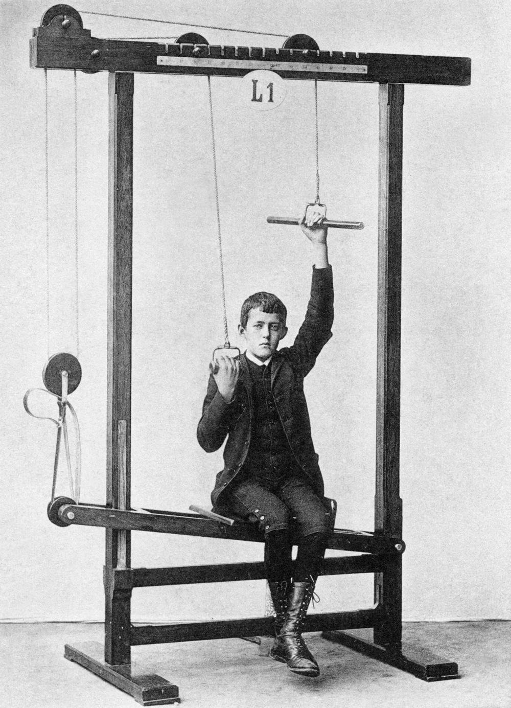 """En av läkaren Gustaf Zanders träningsapparater. Just denna är en så kallad """"armsträckare"""" för sträckning av armen samt balansträning för bålen.  Istället för att personal assisterade patienterna tyckte Zander att mekaniska apparater kunde göra jobbet bättre. En apparat kunde ställas in individuellt och upprepa samma precisa rörelse om och om igen utan att tröttna. Behandlingen blev också mindre kostsam.  Bildkälla: Tekniska museet, okänd fotograf."""
