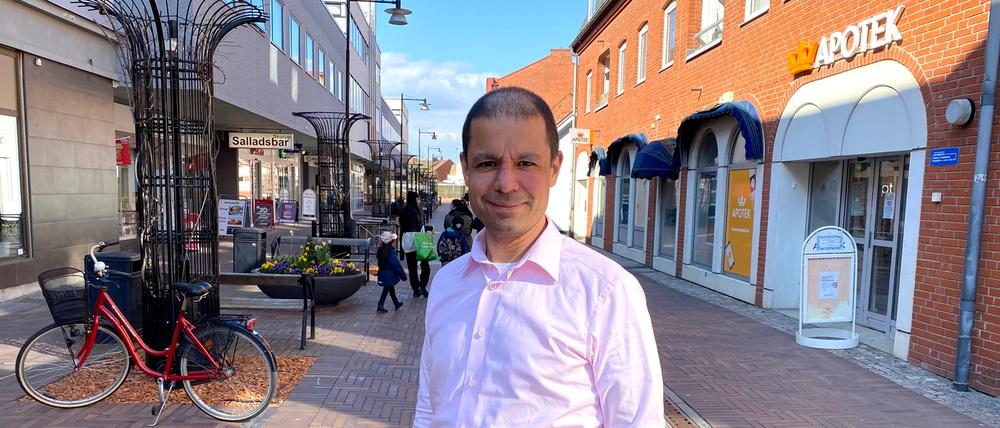 Sahand Kousha står på Stora Torggatan i Skurup. Det är vackert väder och han har mörkt hår och rosa skjorta.