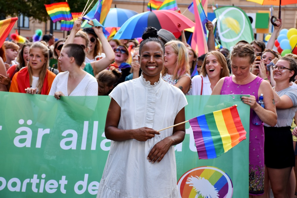 Alice Bah Kuhnke ler medan hon håller i en pride-flagga och går i en Prideparad