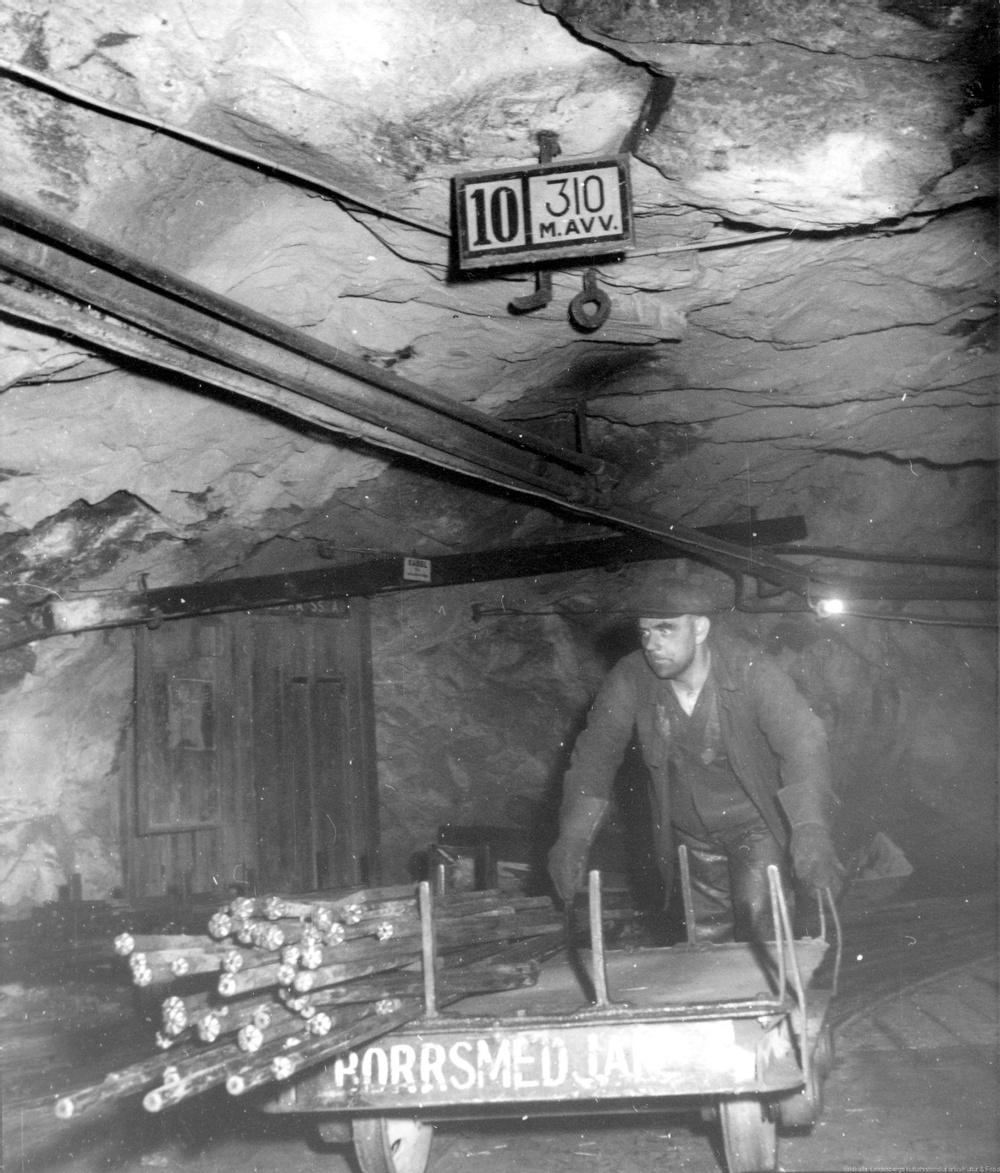 Svartvit bild på en arbetare i borrsmedja i Stripa gruva.