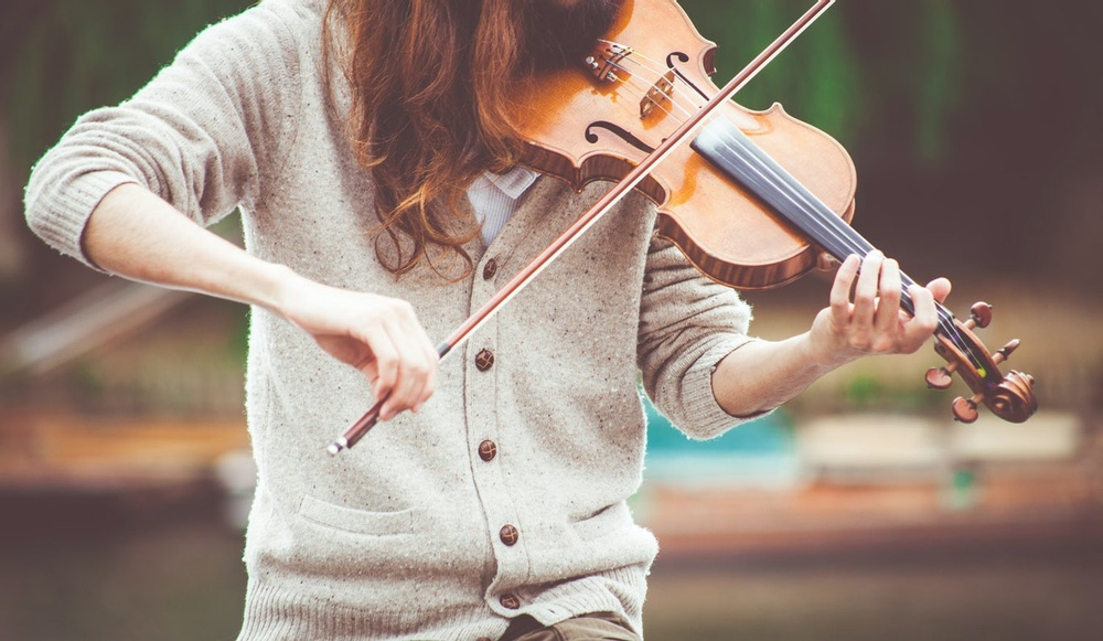 En person med långt hår, men utan ansikte i bild, spelar på en fiol.