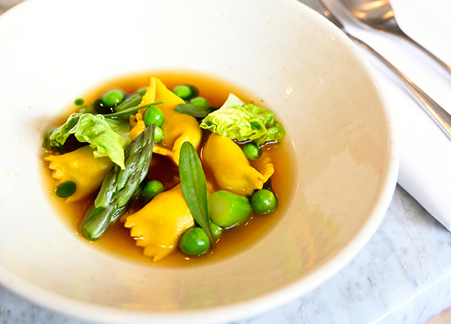 Pea agnolotti, smoked ham consommé, pancetta and baby gem