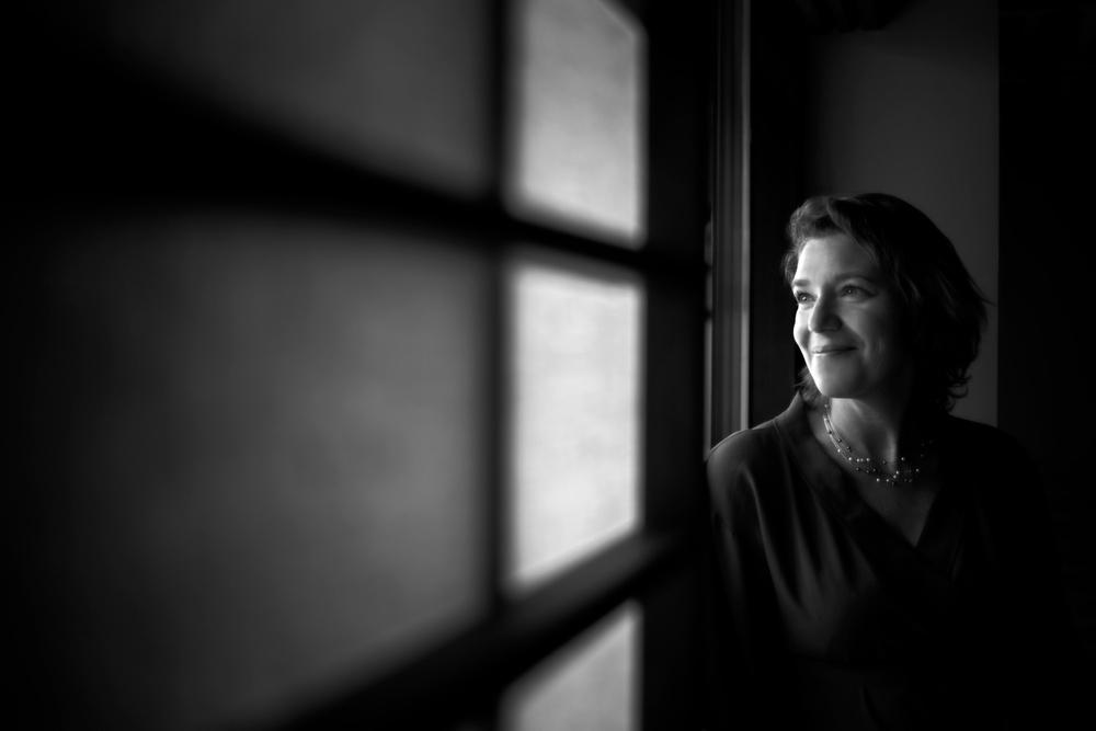 Monika Hilm, vd på Yasuragi sitter vid ett fönster med shojiskärmar.