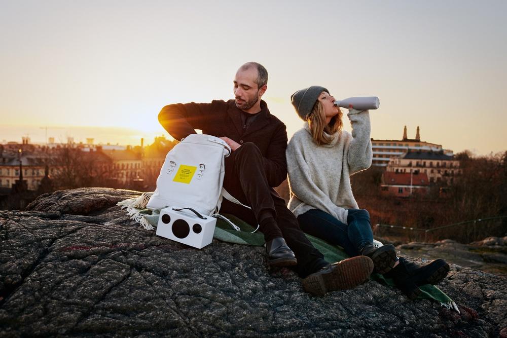 En kvinna och en man har picnic. med designryggsäcken.