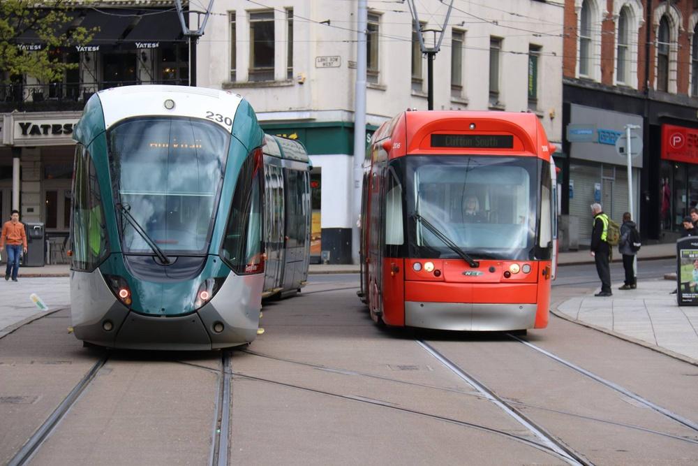 Två olika spårvagnar, en från Alstom (grå) och en från Bombardier (rödfolierad).