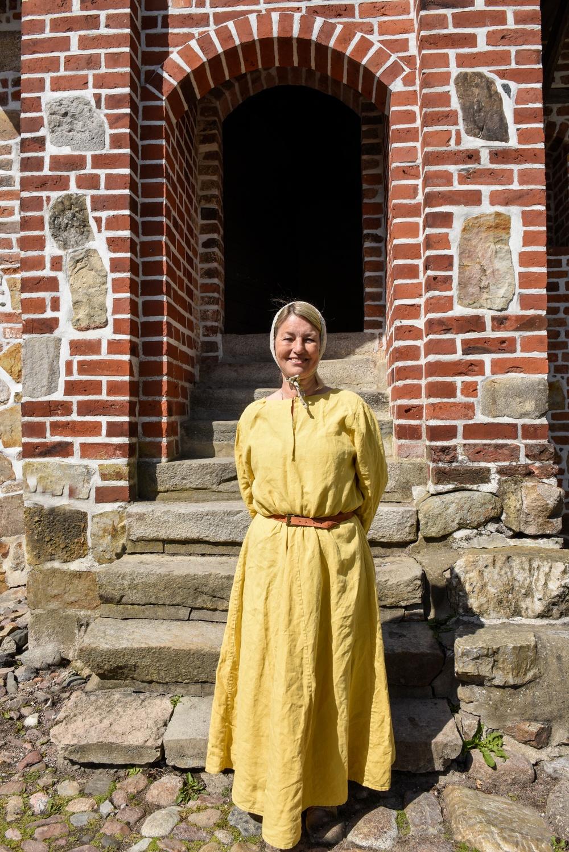 Volontären Marianne Mårtensson framför Dekanhuset på Kulturen i Lund. Foto: Viveca Ohlsson, Kulturen.