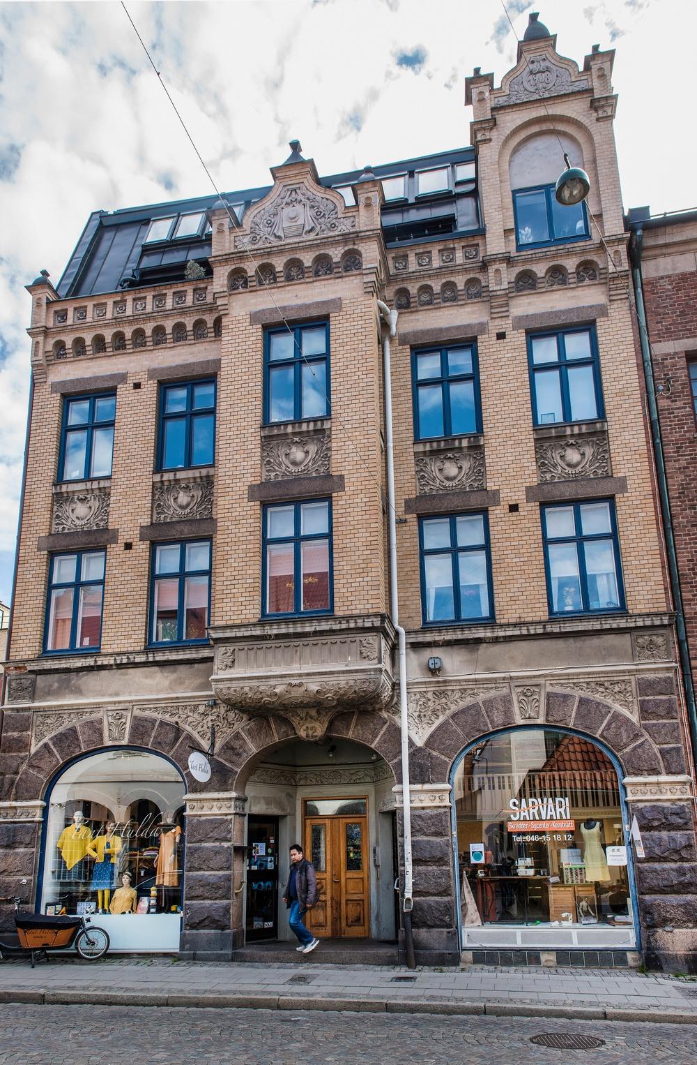 Huset där glasplåtarna hittades byggdes 1908 av den välkända fotografen Maria Jonn. Högst upp fanns en fotoatélje i två våningar. I bottenvåningen fanns, precis som idag, två affärslokaler. I den ena levererades bilderna till fotografens kunder. Över porten är namnet JONN skulpterat och högt upp, huggen i sten, finns en kamera med stativ och skynke. Foto: Viveca Oholsson/Kulturen