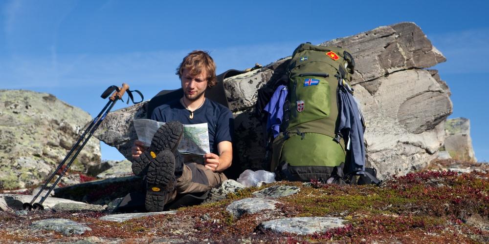 Illustrasjonsfoto/ Shutterstock. Pilegrim sjekker kartet og tar en pause på turen oppover Gudbrandsdalen.