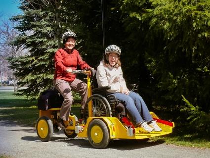Vélo adapté aux personnes à mobilité réduite, sur la piste cyclable. Ici, le vélo permet d'accueillir un fauteuil roulant.