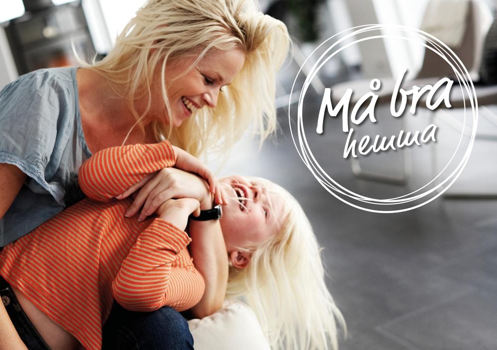En Mamma och dotter busar i en soffa i ett vardagsrum.