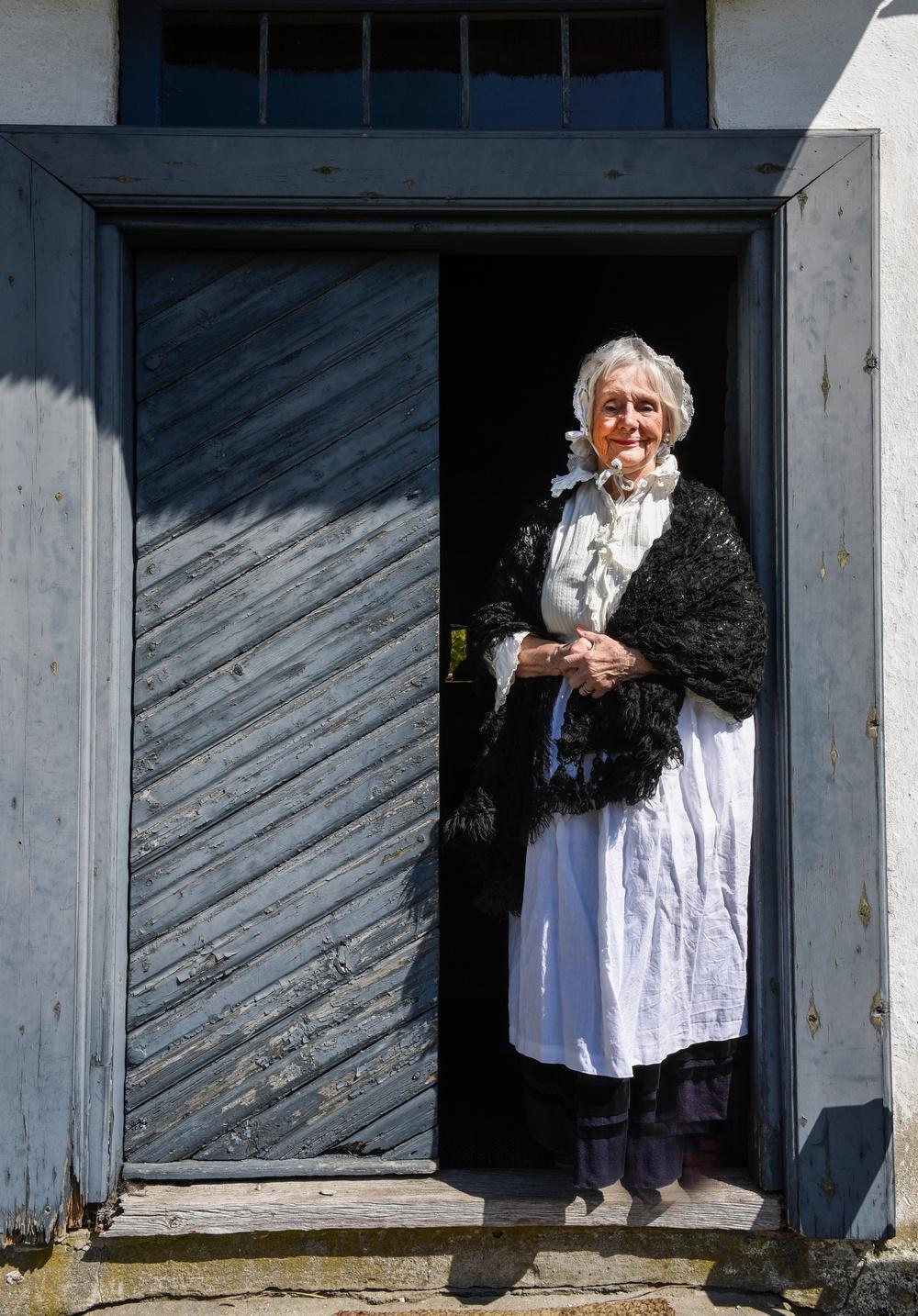 Volontär Ulrika Key i dörröppningen till Västra Vrams prästgård på Kulturen i Lund. Foto: Viveca Ohlsson, Kulturen.