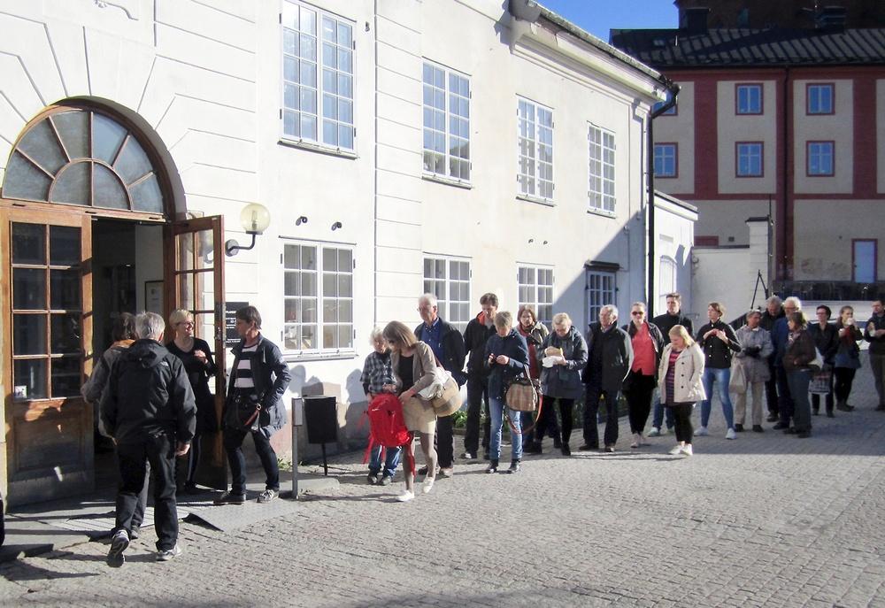 Människor köar för att komma in på Upplandsmuseet.
