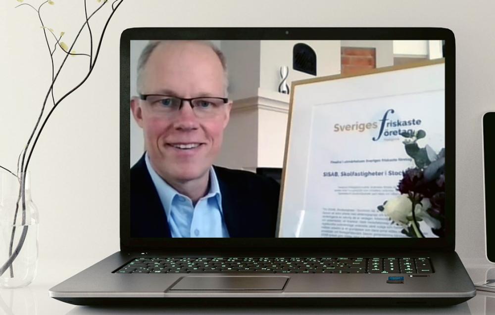 Claes Magnusson tar emot diplom och blommor vid den digitala nomineringen.