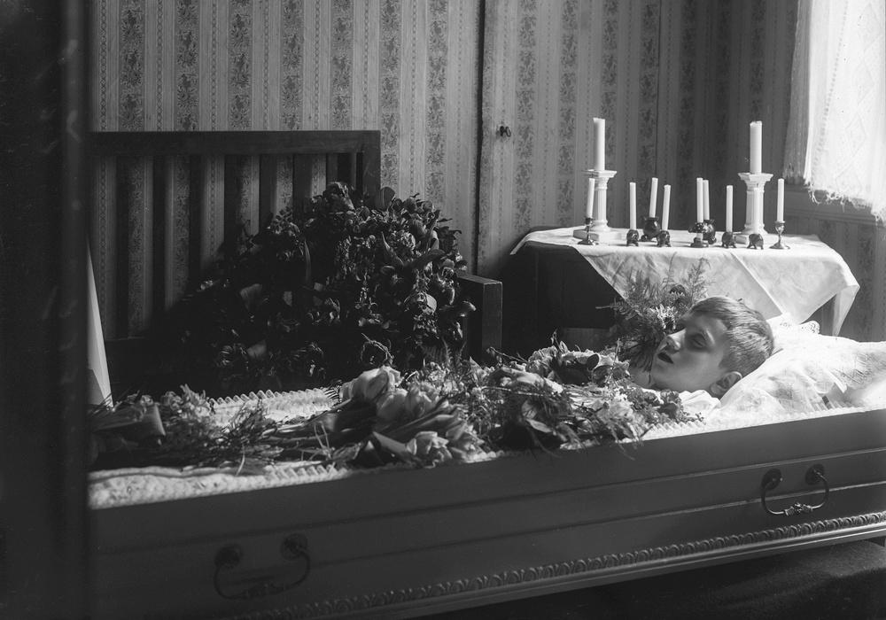 """Foto: Ida Ekelund, ur Kulturens samlingar.  Fotografiet föreställer Emilia Harrings dotterson, Per Hallengren. Dödsannonsen var införd tisdag den 8 mars och onsdag den 8 mars 1927 med texten: """"Min älskade dotterson Per Hallengren har i dag hastigt avlidit i en ålder av 8 1/2 år, djupt sörjd och saknad av mig, många släktingar, kamrater och vänner. Lund den 8 mars 1927. Låten barnen komma till mig och förmenen dem icke, ty sådana hörer Guds rike till. Herren gav och Herren go, välsignat vare Herrens namn. Emilia Harring f Witt."""" Den 11 mars samma annons med tillägget: """"Jordfästningen äger rum i Norra Kyrkogårdens kapell söndagen den 13 mars kl 1 em"""".  Per Hallengren föddes i Landskrona, blev tidigt föräldralös och bodde därför hos sin mormor i Lund."""