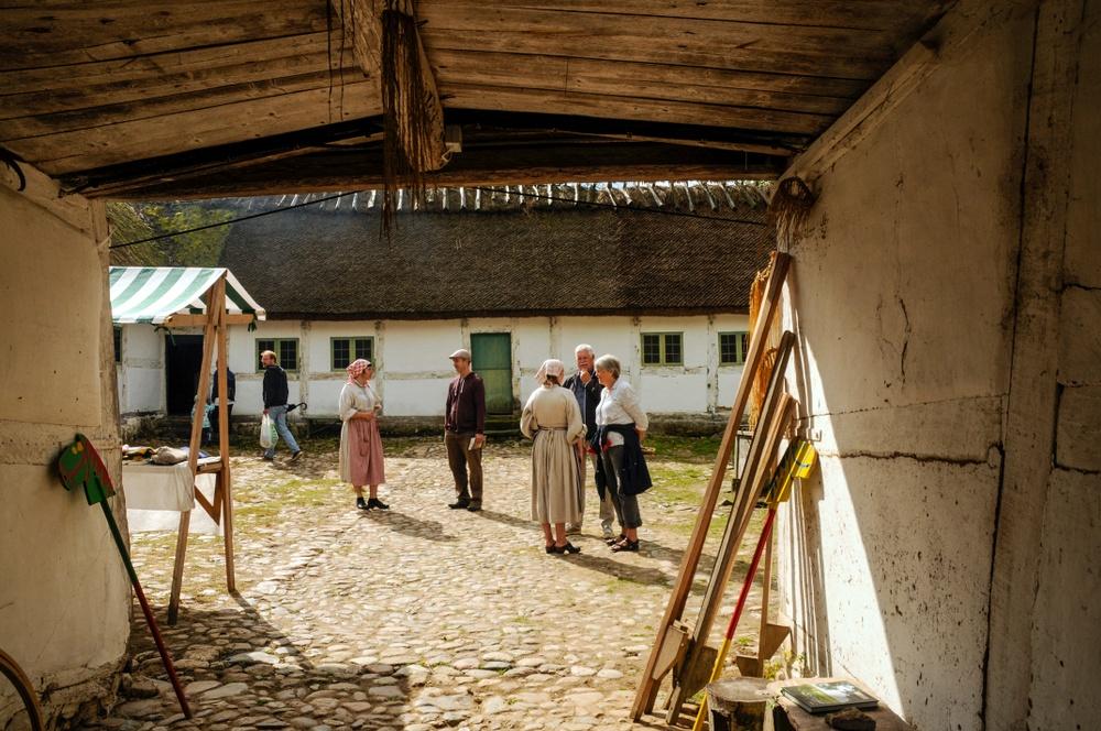 Värdar samtalar med besökare på Gamlegårds innergård på Kulturens Östarp. Foto: Viveca Ohlsson/Kulturen