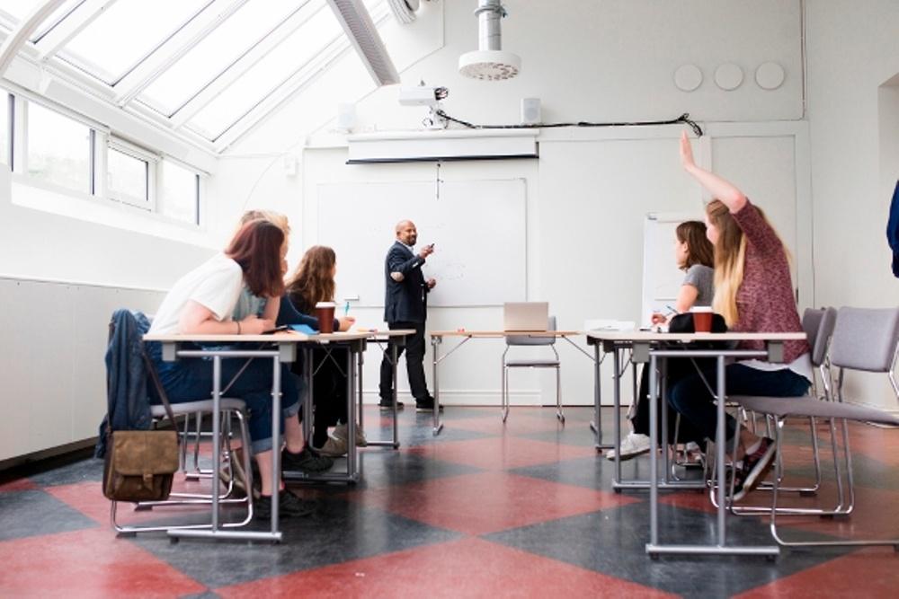 Vuxna elever och lärare i klassrum