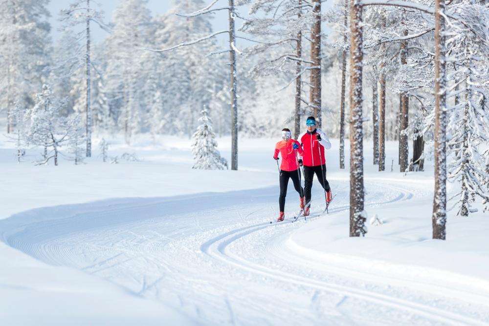 Två personer åker längdskidor i skogarna i Orsa Grönklitt