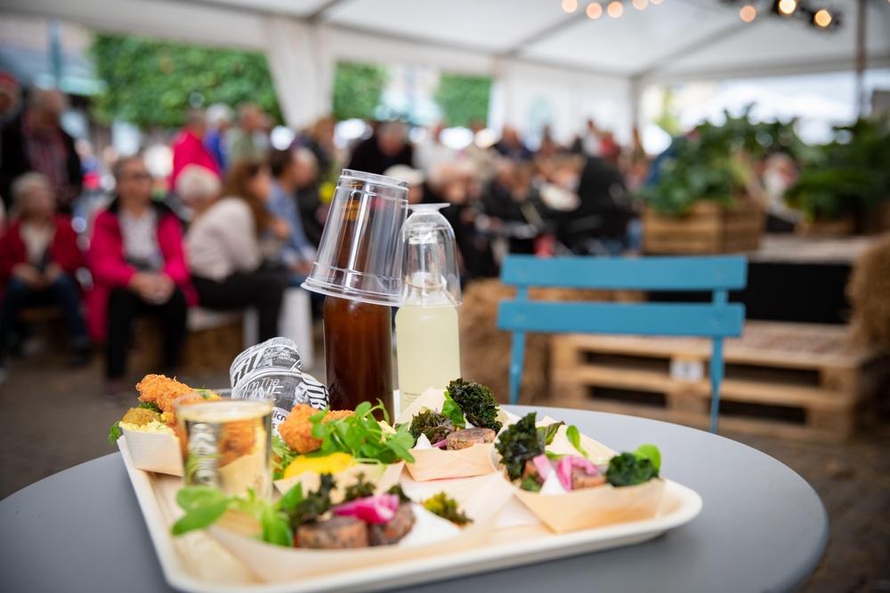 En tallrik med lokala råvaror och lokal mat, lagad och serverad under Falkenberg matdagar. I bakgrunden sitter besökare och äter.