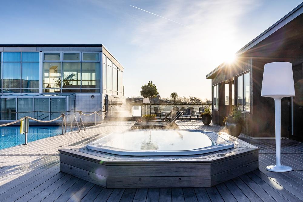 Nybyggt bastuhus till höger, ny varm massagepool rakt fram, åretruntanpassad pool till vänster.