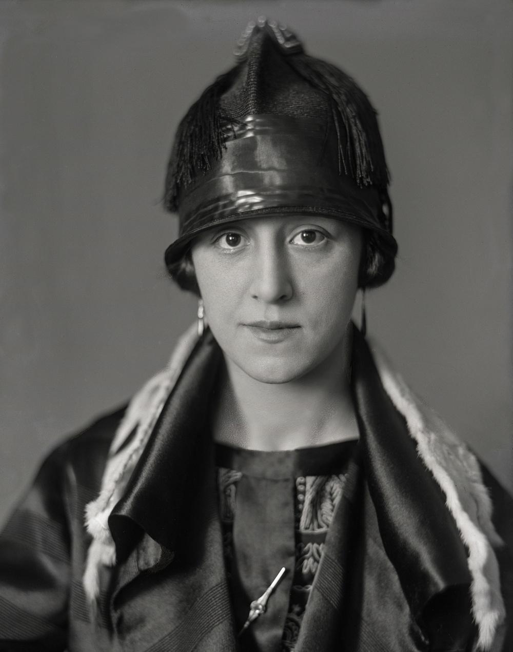 Lilian Borglin i randig klänning, blus med stiliserat blommönster och brosch. Hatten är närmast en hjälm med fransar och långt nerdragen. Den vita kragen som ligger över hennes axlar är hermelinskinn.                                      Fotograf Ida Ekelund, Lund, 1920-talet. Inköpt av Kulturen 2013.  Glasplåt (13 x 18 cm) skannad för utskrift.