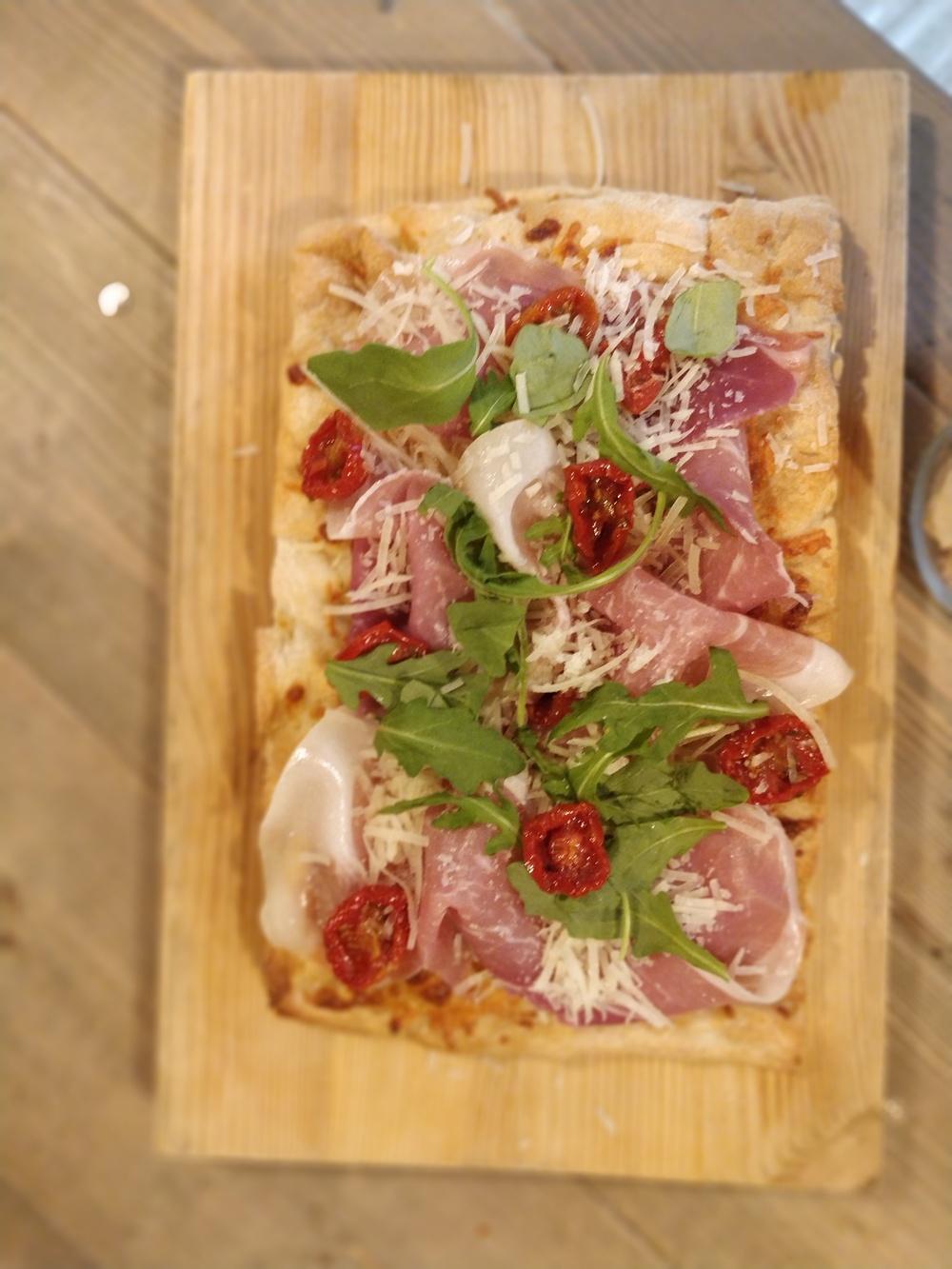 SCROCCHIARELLA PROSCIUTTO Luftigt och frasigt surdegsbröd från Italien med långlagrad ost och mozzarella, toppad med prosciutto, semitorkade tomater och ruccola. 99 kr